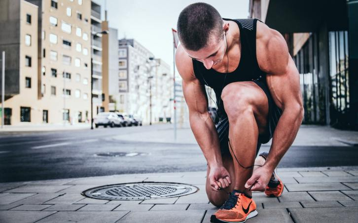 Male Runner Kneeling to Tie Shoe | RhodesPT.net
