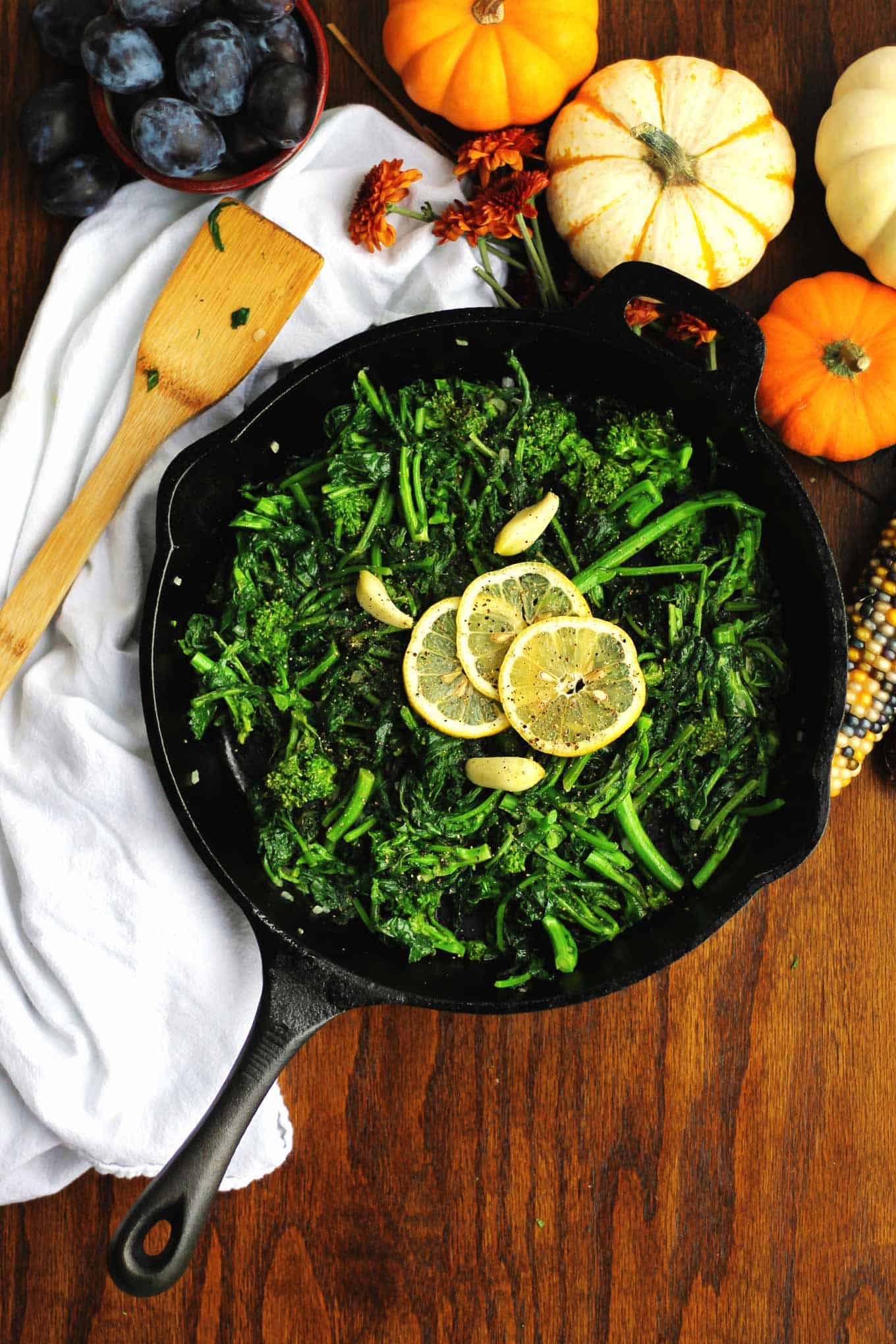 sauteed broccoli rabe and kale in a black skillet with lemon