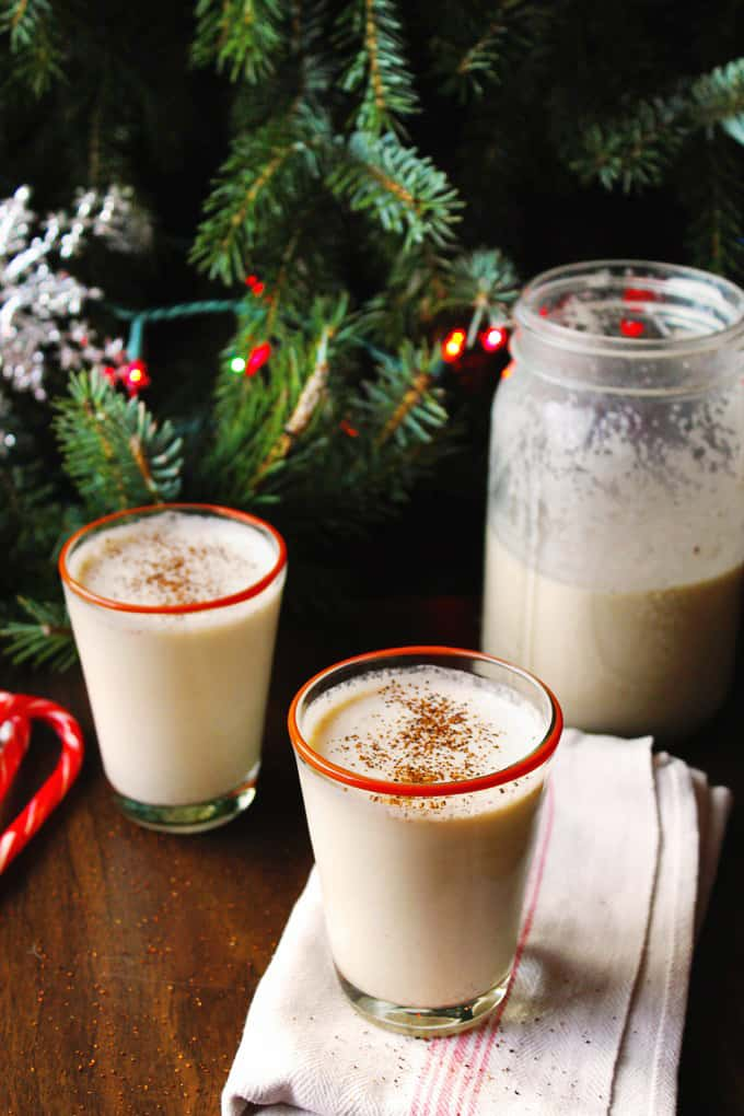 some homemade eggnog in front a christmas tree. best eggnog recipe
