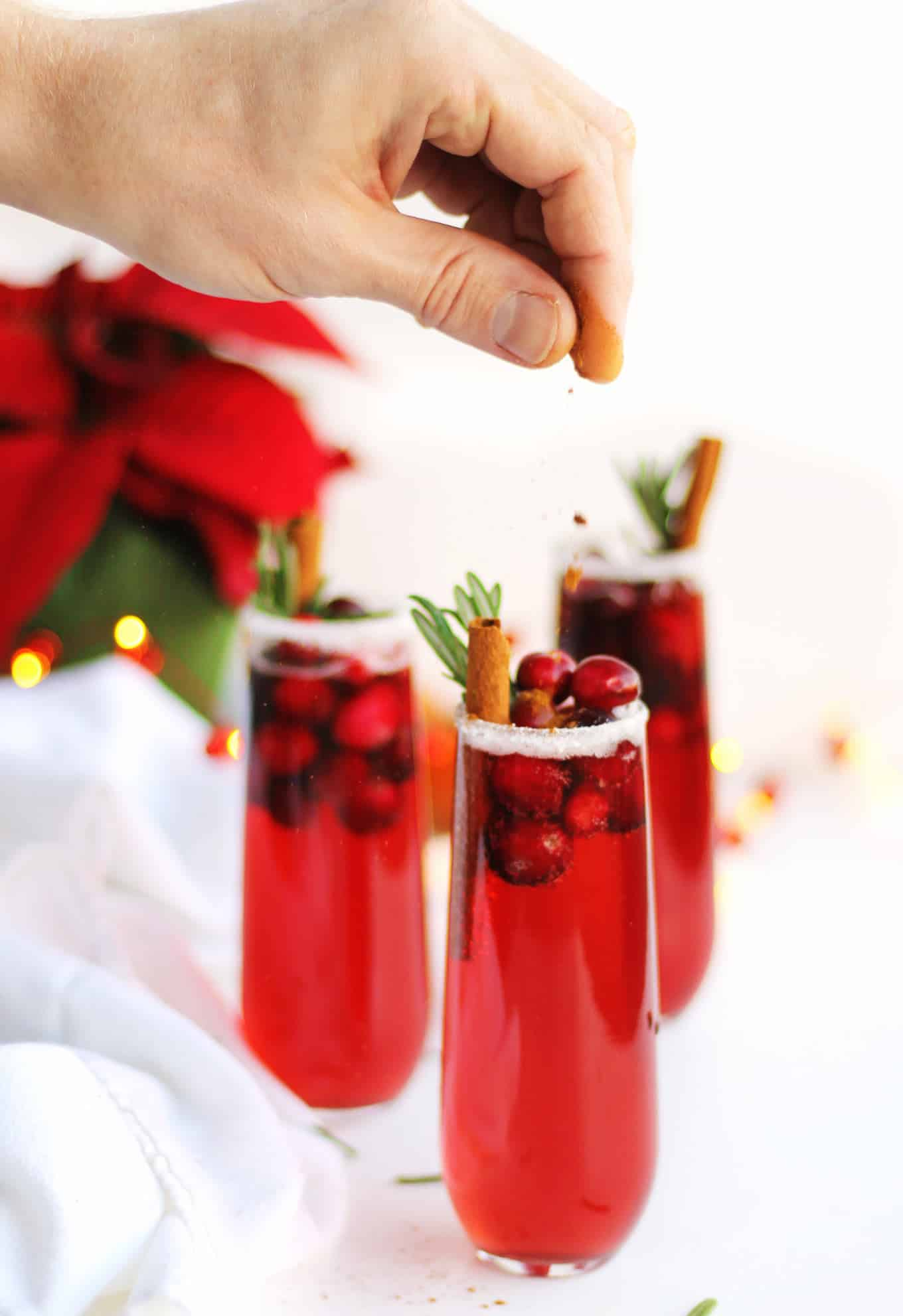 sprinkling cinnamon onto a holiday cranberry mimosa