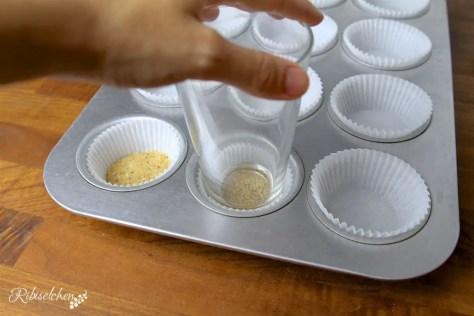 Nussmasse wird in Muffinsförmchen gedrückt