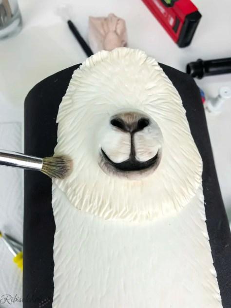 Der Lama Kopf wird mit einem Pinsel bemalt