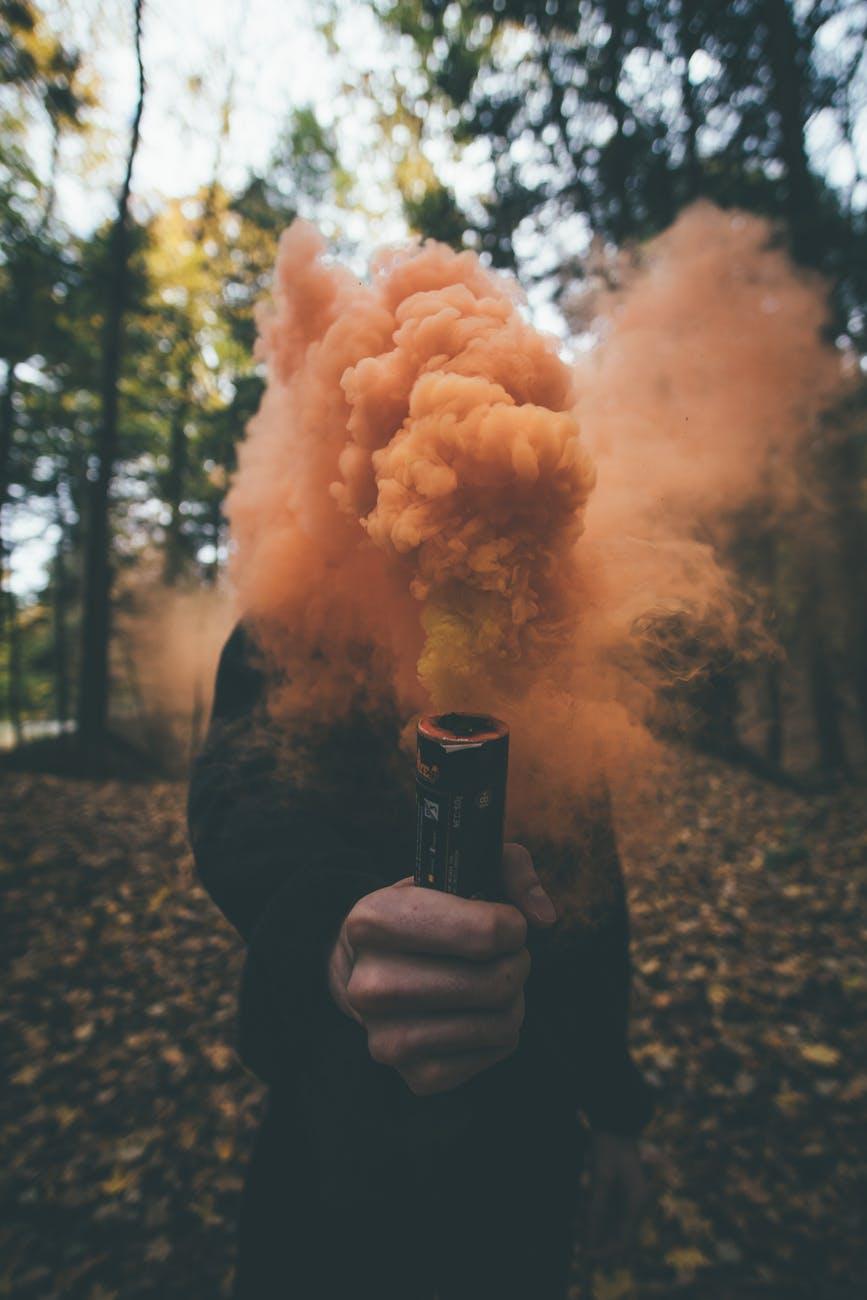 person holding orange smoke bomb