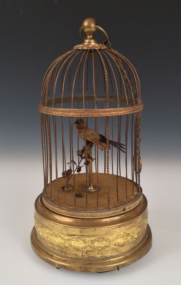 ANTIQUE SINGING BIRD IN CIRCULAR BRASS CAGE