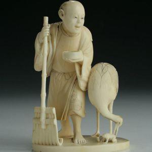 JAPANESE IVORY OKIMONO OF A MAN AND CRANE