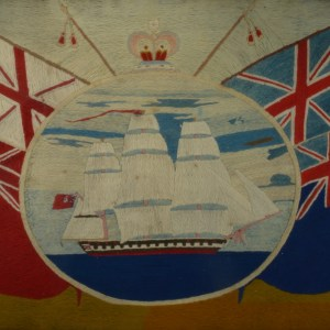 ANTIQUE SAILOR'S OVAL WOOLWORK PICTURE SHIP AND FLAGS