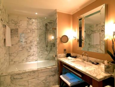 St Pancras Hotel guest bathroom - marble tiling, shower/bath and vanity