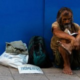 Image of a homeless man sitting on the street