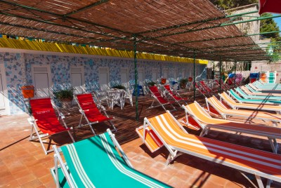 deck loungers in a line on terrace with beach huts behind, capri