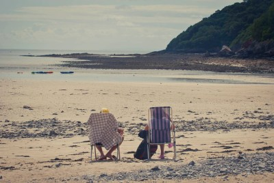 sat alone in deckchairs on beach at oxwich gower wales