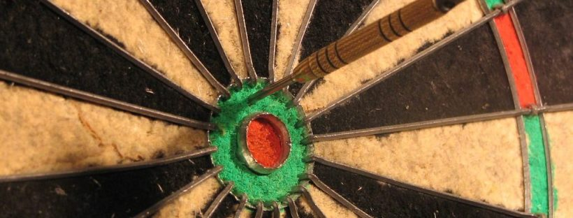 dartboard with a couple of darts stuck in it, but not in the bullseye