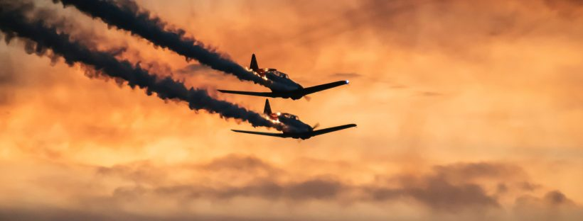 two single-engine aircraft flying toward the horizon against the backdrop of a sunset