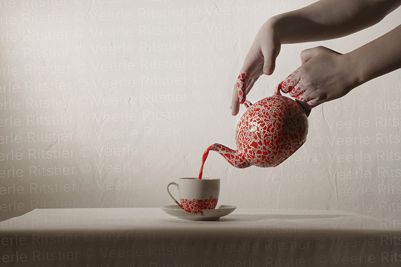 Photo called Primordium VII. With a tea cup, and female hand holding a teapot covered with hand painted red particles, made by Veerle Ritstier