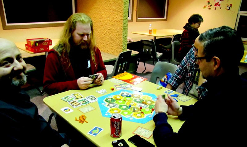 Dan, Chris, Paul, and Michael playing Settlers of Catan. Sandy is lurking in the background, playing something else.