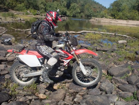 One of the riders in our group crossing the Little River stream bed. The damaged bridge is in the background.