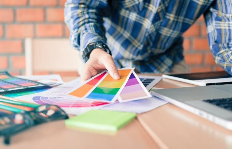 Designer choosing colors for doing graphic on laptop.