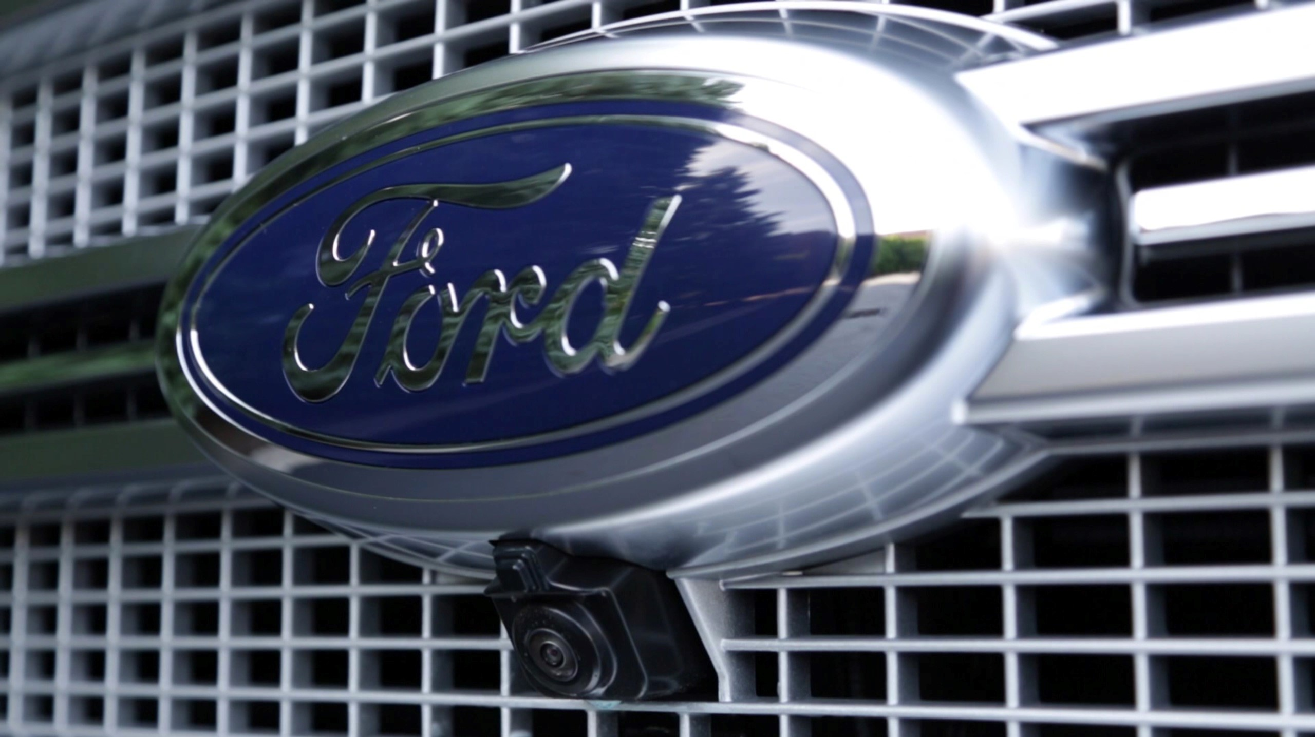 The accessible front-view camera on name F-150 models lay discretely next a Ford badge.