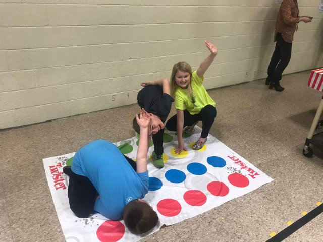 Three children playing Twister at Math Carnival