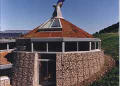 A circular building uses trapions for cladding its outer walls.