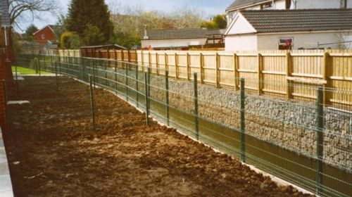 A gabion retaining wall is used on either side of this river