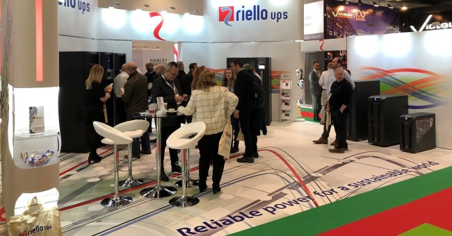 Riello UPS exhibition stand at DCW 2019 (Data Centre World) team talking to 20 IT professionals
