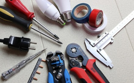 Variety of electrician's tools arranged in a circle (screwdrivers, wire cutters, pliers)