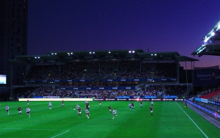football match being played at night in stadium with floodlights