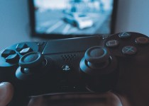 close up of a playstation controller with a TV in the background