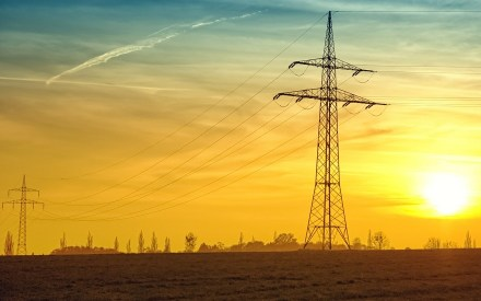 Electricity transmission power lines with bright sun setting in the backgroud