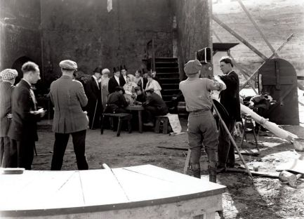 View of an outdoor set at Universal Studios in 1925, with Park Ries cranking the camera