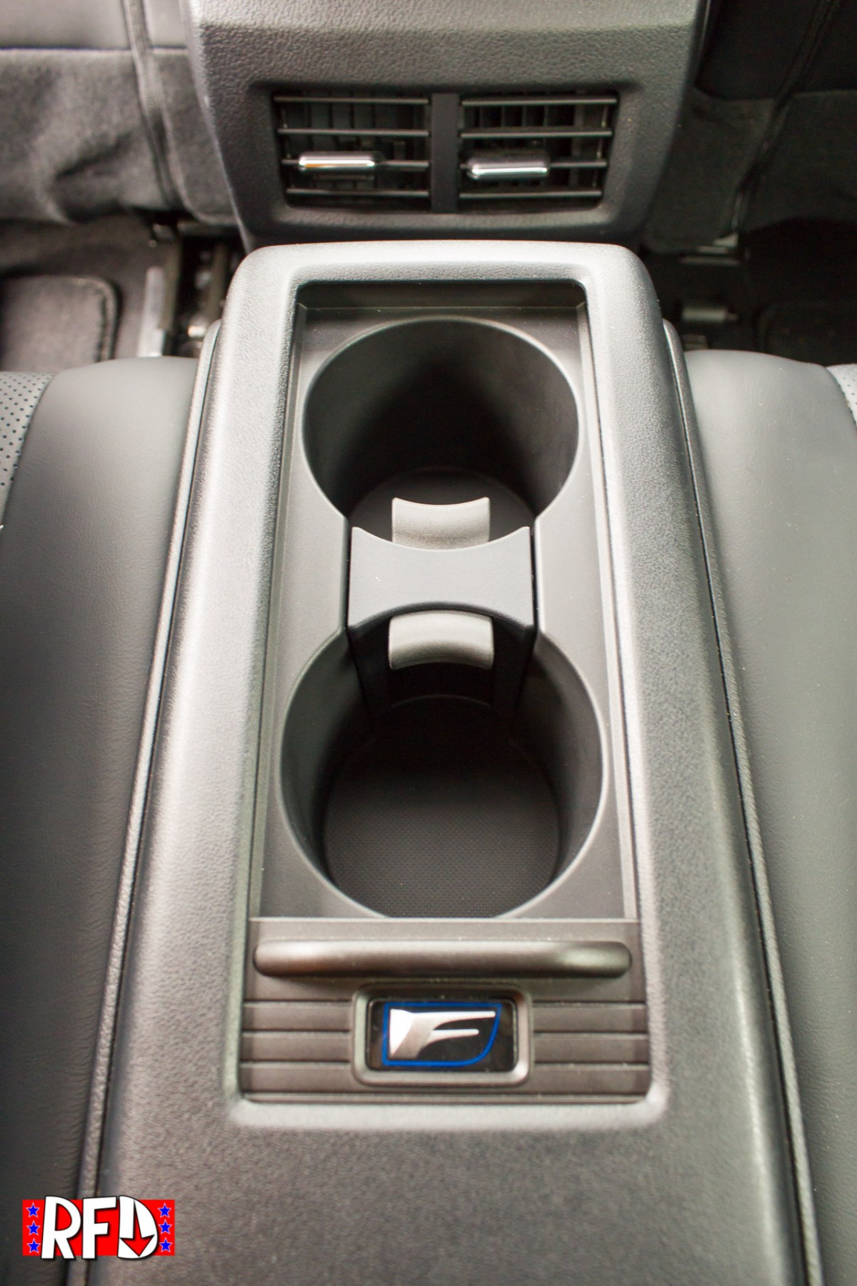 2016 Lexus RC F rear center console with cup holders and F Sport badge.