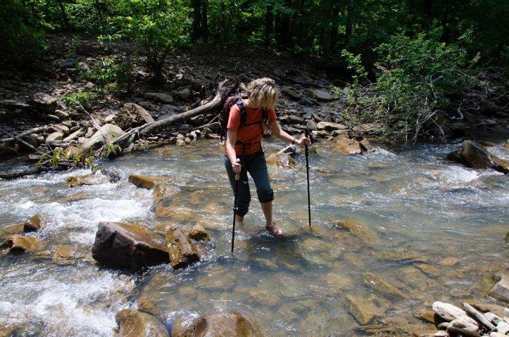 A hiker crosses Falling Water Creek