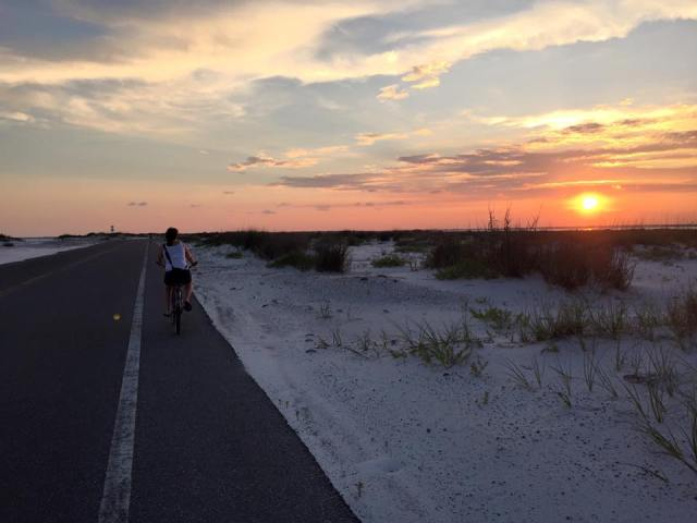 A woman rides a bike on the island at sunset