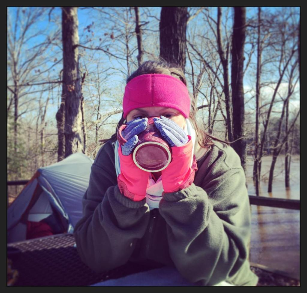 A woman sips hot cocoa while camping