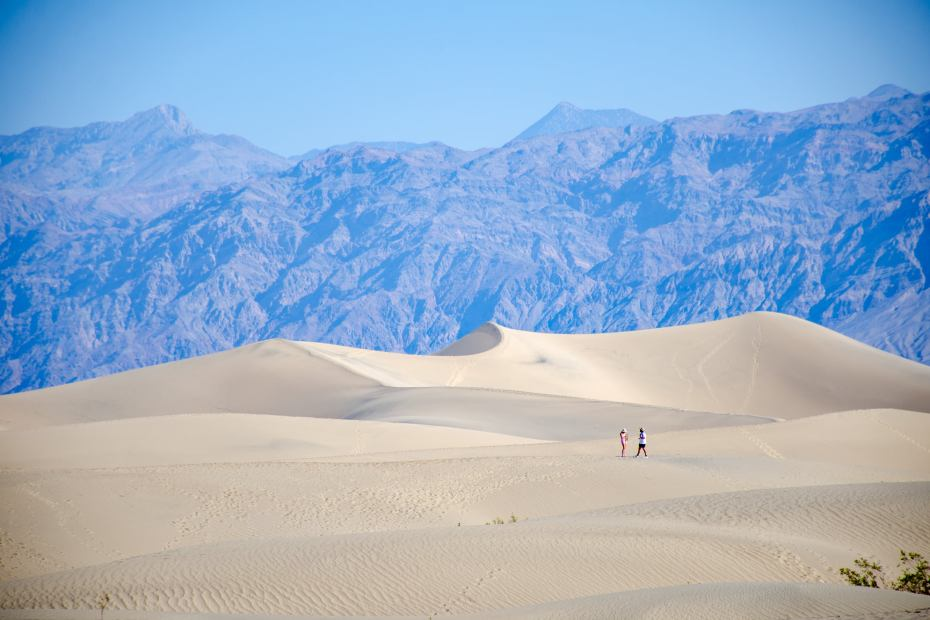hikers enjoy the sand dunes at Death Valley National Park in the summer