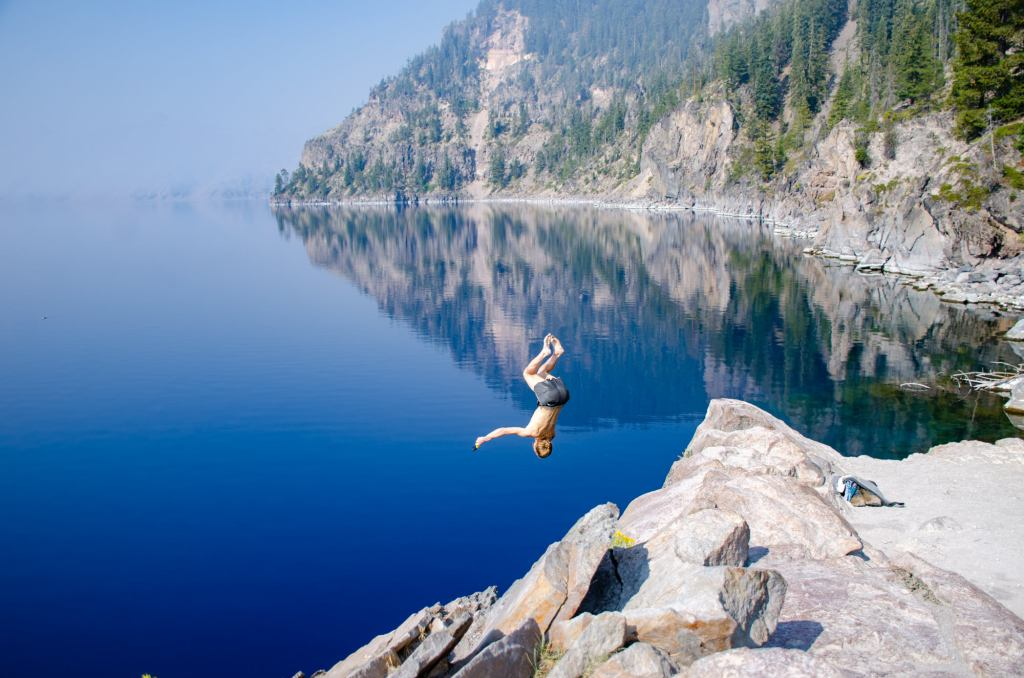 A man does a backflip into Crater Lake