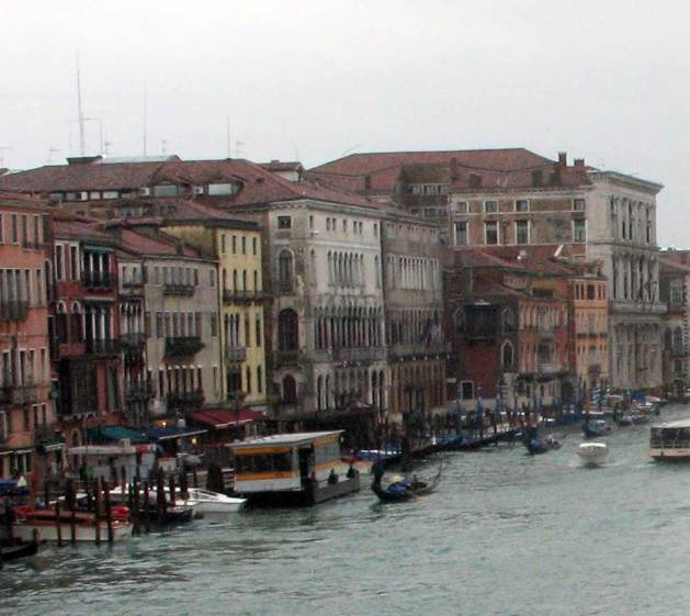 East bank of the Grand Canal, looking south from the Rialto Bridge. The two buildings to the right of the yellow facade are the Ca' Corner Loredan and the Ca' Farsetti, both built in the the early 13th century (and later modified). These are the earliest major palazzi facing the Grand Canal.