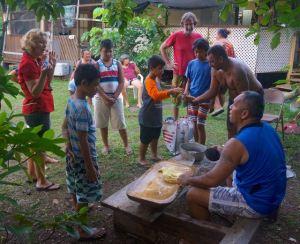 Denis prepares fresh roasted breadfruit poi in fresh coconut milk for all to savor.