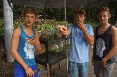 Rainer Dawn, Bryce and Trent Rigney munching fruit with baby rabbits.
