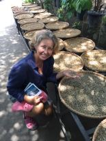 Leslie Rigney in front of drying Lewak Coffee