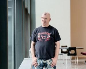 Professori poseeraa kameralle aulassa. A professor poses for a camera in a lobby.