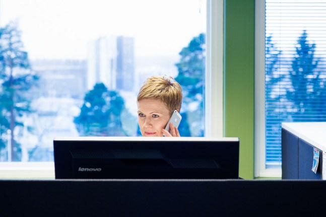 nainen puhuu puhelimeen tietokonenäytön takana. Woman talking on the phone behind a monitor.