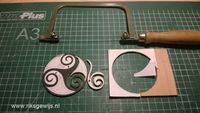 Doordat ik de vector met de hand heb bijgewerkt naar een eigen ontwerp voor de tol kan deze op het hout gelijmd worden en uitgezaagd. Ik gebruik gewoon een pritt-stift om dit vast te zetten. Straks kan ik dat makkelijk verwijderen.