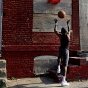 In this April 8, 2013 picture, a boy shoots a basketball into a makeshift basket made from a milk crate and attached to a vacant row house in Baltimore. The U.S. Census Bureau estimates that 20 percent of American children are impoverished. An estimated 16,000 buildings are vacant or abandoned in Baltimore. (AP Photo/Patrick Semansky)