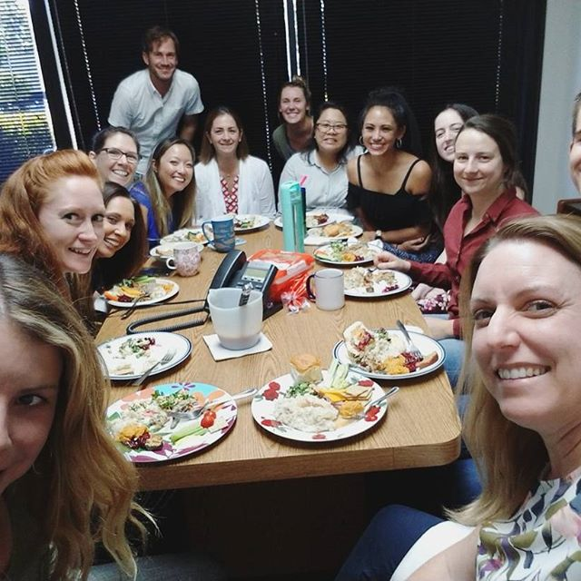 Group of people in an office with food.