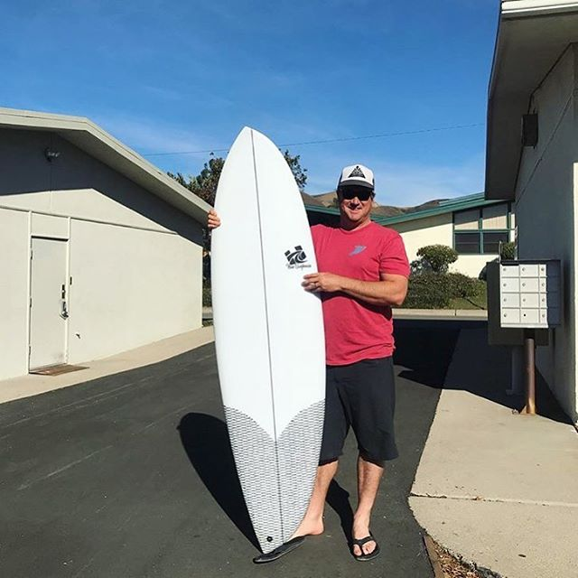 Man holding surf board in a parking lot.