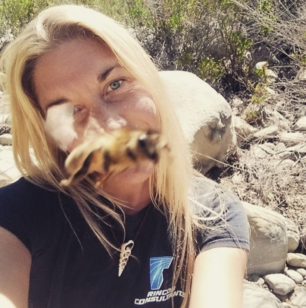 A woman with a bee flying in front of her face.