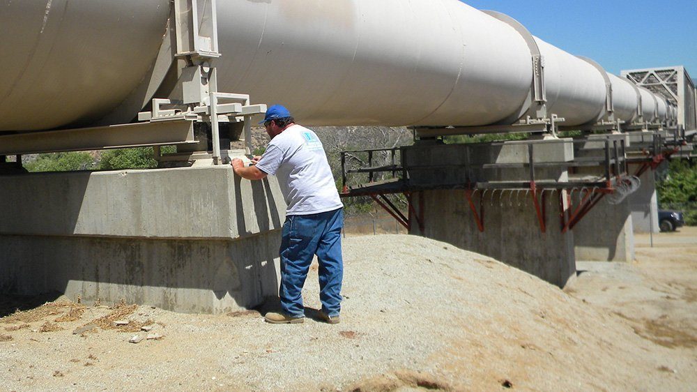 Man standing next to a water pipe filling out a form.