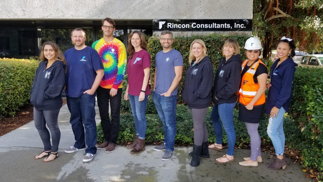 Group of people standing outside of an office wearing their Rincon logo gear.