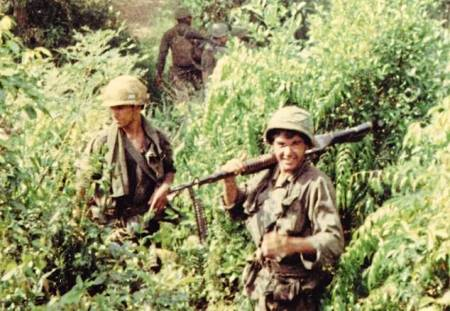 Oliver Stone, right, shouldering an M60 machine gun in Vietnam